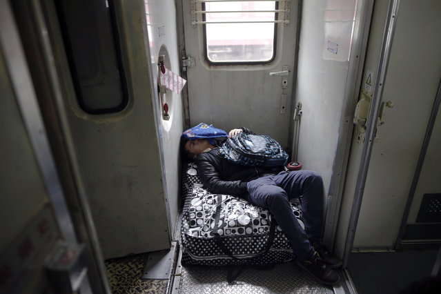 A passenger sleeps on his baggage inside a train from Shanghai to Shijiazhuang at the station in Suzhou, China, January 27, 2016, after migration for the annual Chinese Lunar New Year and Spring Festival began. (Photo by Aly Song/Reuters)