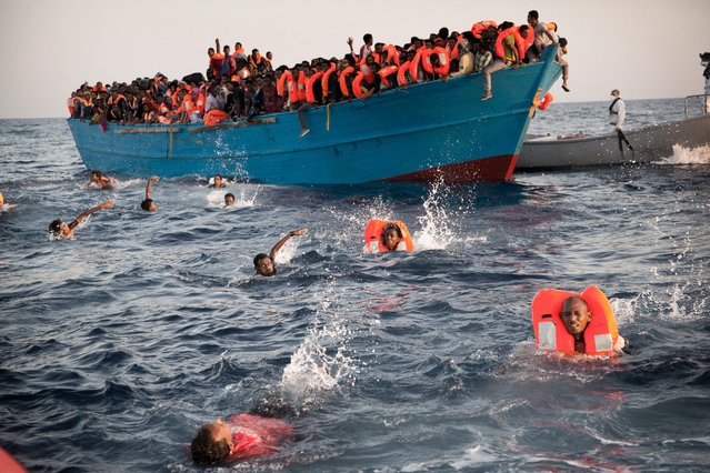 Migrants, most of them from Eritrea, jump into the water from a crowded wooden boat as they are helped by members of an NGO during a rescue operation in the Mediterranean sea, north of Sabratha, Libya, Monday, August 29, 2016. (Photo by Emilio Morenatti/AP Photo)