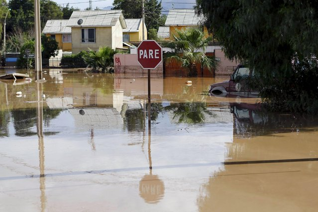 A traffic signal is seen on a flooded street at Copiapo city, March 26, 2015. (Photo by Ivan Alvarado/Reuters)