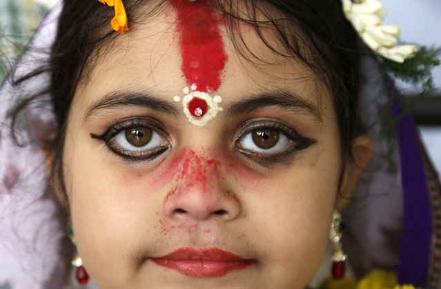 "A young Hindu girl sits for a ceremony where she and other girls are worshipped as ""Kumari"", or living goddess, during Ram Navami festival, at a temple in Kolkata, India, Saturday, March 28, 2015. (Photo by Bikas Das/AP Photo)"