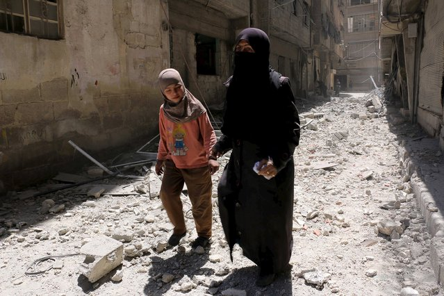 Residents walk upon the rubble of collapsed buildings after what activists said was shelling by forces loyal to Syria's President Bashar al-Assad at Ain Tarma in eastern Ghouta, a suburb of Damascus, Syria April 26, 2015. (Photo by Amer Almohibany/Reuters)