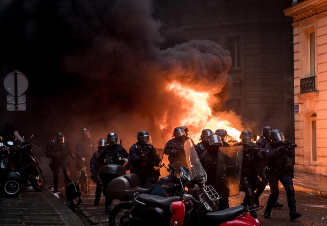 "Police run past a burning car as they push protesters back during the ""yellow vests"" demonstration near the Arc de Triomphe on December 8, 2018 in Paris France. (Photo by Chris McGrath/Getty Images)"
