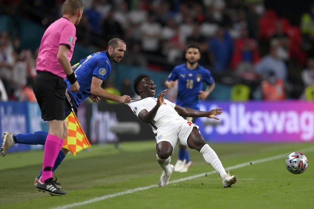 Italy's Giorgio Chiellini, left, stops England's Bukayo Saka during the Euro 2020 soccer final match between England and Italy at Wembley stadium in London, Sunday, July 11, 2021. (Photo by Laurence Griffiths/Pool via AP Photo)