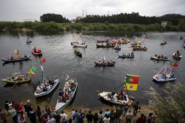 """Boats arrive to receive the benediction during the festivity of """"Nossa Senhora da Boa Viagem"""", in Constancia April 6, 2015. This benediction has been held annually for about 200 years. In the past, goods were transported by the Tagus river in small boats to Lisbon, 100 km south. The sailors, as the navigation was dangerous, blessed their boats every year during the festivity of  """"Nossa Senhora da Boa Viagem"""". (Photo by Rafael Marchante/Reuters)"""