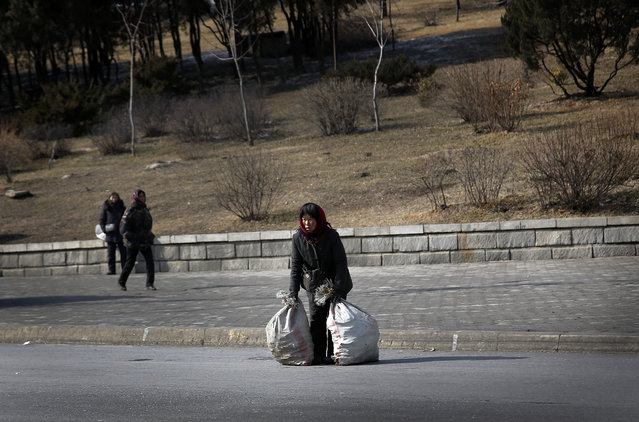 An North Korean woman crosses the street with her belongings packed in sacks on Sunday, February 14, 2016. (Photo by Wong Maye-E/AP Photo)