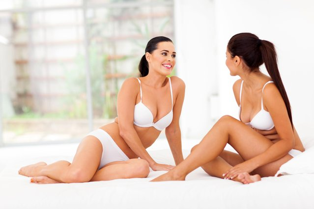 Two women friends in underwear sitting on bed. (Photo by Michael Jung/Alamy Stock Photo)