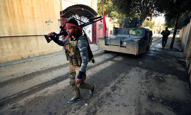 A member of Iraqi rapid response forces holds his weapon during battle with Islamic State militants in the Mithaq district of eastern Mosul, Iraq, January 4, 2017. (Photo by Thaier Al-Sudani/Reuters)