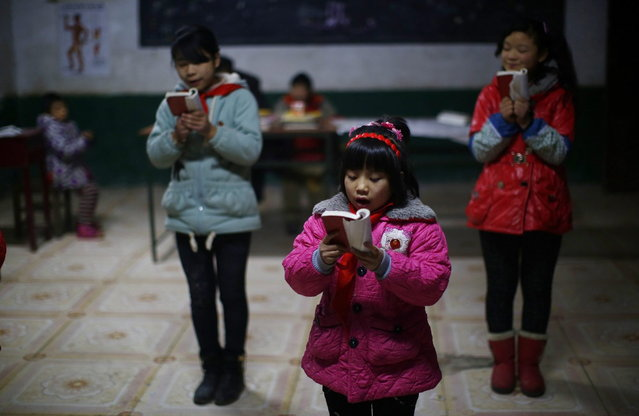 "Students read a lecture from Mao Zedong's ""Little Red Book"" at the Democracy Elementary and Middle School in Sitong town, Henan province December 3, 2013. (Photo by Carlos Barria/Reuters)"