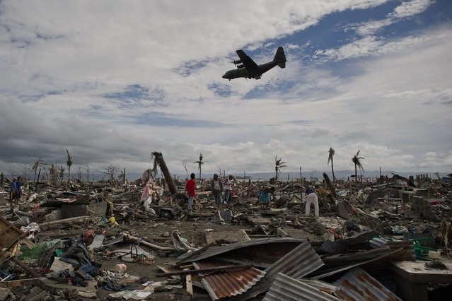 Super Typhoon Haiyan victims sift through the rubble of their destroyed homes as a military cargo plane flies over head in Tacoblan on November 20, 2013. (Photo by Nicolas Asfouri/AFP Photo)
