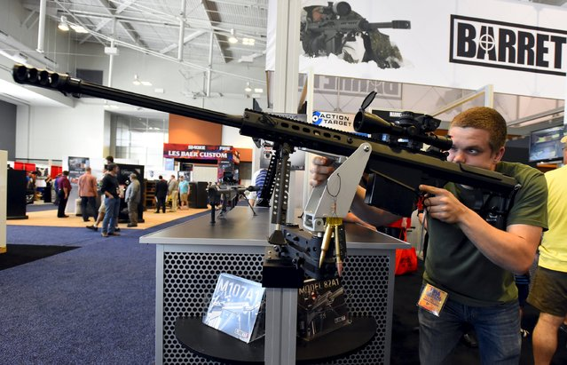 Blake Scherrer looks at a Barrett .50 caliber rifle in the trade booths showroom during the National Rifle Association's annual meeting in Nashville, Tennessee April 12, 2015. (Photo by Harrison McClary/Reuters)