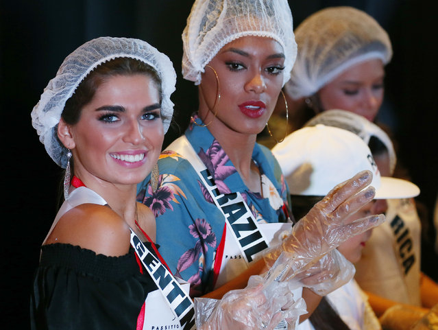 Miss Universe contestants Estefania Bernal of Argentina and Raissa Santana of Brazil, wear plastic gloves as they pack meals for the needy in suburban Pasay city southeast of Manila, Philippines Wednesday, January 18, 2017. (Photo by Bullit Marquez/AP Photo)