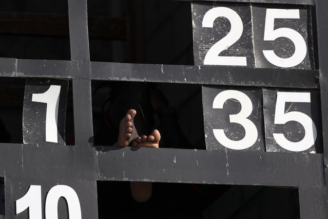 A group worker rests at the scoreboard during day one of the third cricket Test match between England and West Indies at the Daren Sammy Cricket Ground in Gros Islet, St. Lucia, Saturday, February 9, 2019. (Photo by Ricardo Mazalan/AP Photo)