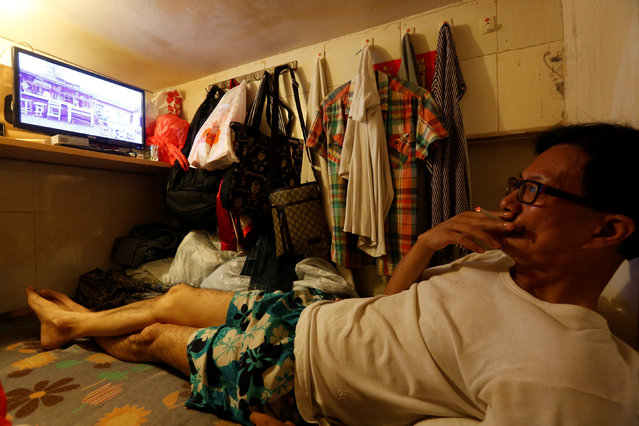"""Unemployed Hong Kong resident Simon Wong, 61, watches TV inside his 4-by-6-feet partitioned unit, or """"coffin unit"""", with a monthly rent of HK$1,750 ($226) in Hong Kong, China October 31, 2016. (Photo by Bobby Yip/Reuters)"""
