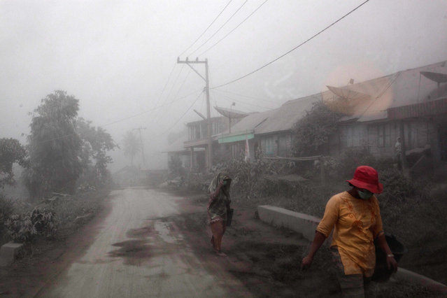 Villagers walk on the road as their village is hit by ash from the eruption of Mount Sinabung in Payung village on January 8, 2014 in Karo District, North Sumatra, Indonesia. (Photo by Ulet Ifansasti/Getty Images)
