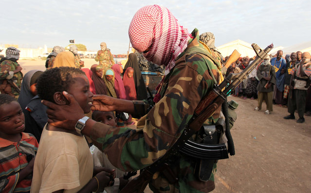 A Somali-based militant group officially affiliated to core al Qaeda.  Caption: Members of al Shabaab distribute relief to famine-stricken internally displaced people at Ala Yaasir camp September 3, 2011. (Photo by Feisal Omar/Reuters)