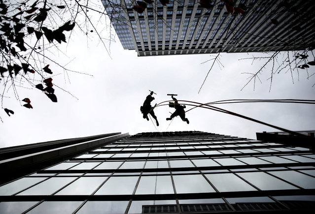 Window cleaners, dressed as a dog (R) and wild boar, this year's and next year's Chinese zodiac animals, pose while cleaning the windows of Ryumeikan hotel during a promotional event to celebrate the upcoming new year in Tokyo, Japan, December 13, 2018. (Photo by Kim Kyung-Hoon/Reuters)