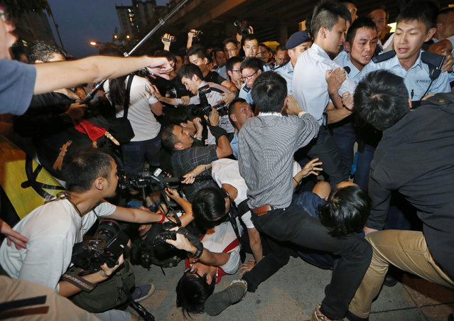 Pro-democracy protesters and photographers fall on the ground after being pushed by police officers as Hong Kong Chief Executive Leung Chun-ying arrives at a rally to support the government's political reform proposal in Hong Kong Wednesday, April 22, 2015. (Photo by Kin Cheung/AP Photo)