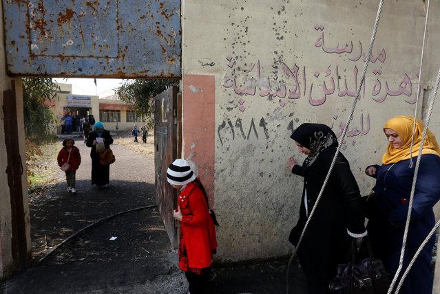Parents of schoolchildren walk to register their children in school in Mosul, Iraq, January 23, 2017. (Photo by Muhammad Hamed/Reuters)
