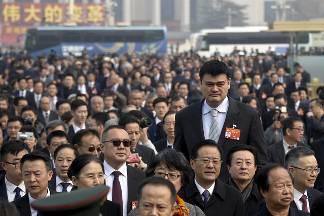 Former NBA basketball player Yao Ming, left, a delegate to the Chinese People's Political Consultative Conference (CPPCC), towers over other delegates as they arrive at the Great Hall of the People to attend the opening session of the CPPCC in Beijing, Sunday, March 3, 2019. (Photo by Andy Wong/AP Photo)