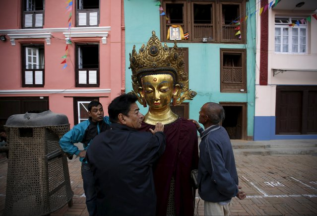 Devotees stand near an idol of Buddha during the Samyak festival in Lalitpur, Nepal, March 11, 2016. (Photo by Navesh Chitrakar/Reuters)