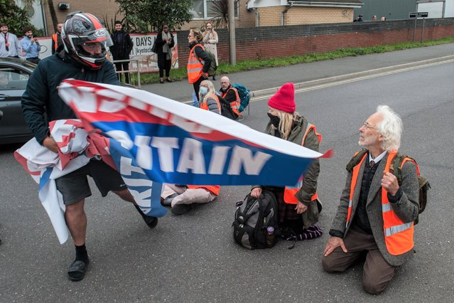 An angry motorist snatches a banner from Insulate Britain protesters blocking a junction near the Dartford Crossing on October 13, 2021 in Thurrock, England.(Photo by Guy Smallman/Getty Images)