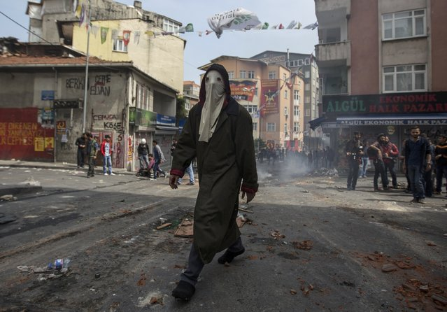 A masked protester walks during clashes with police in Okmeydani neighbourhood in Istanbul, Turkey, May 1, 2015. (Photo by Kemal Aslan/Reuters)