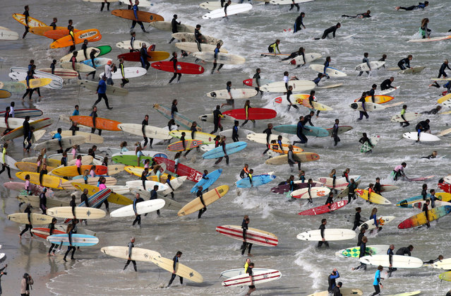 Hundreds of surfers take to the water in an attempt to break the Guinness World Record for the most surfers on one wave at Muizenberg in Cape Town September 17, 2006. (Photo by Mike Hutchings/Reuters)