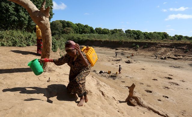 A girl carries a jerry can of water from a shallow well dug from the sand along the Shabelle River bed, which is dry due to drought in Somalia's Shabelle region, March 19, 2016. (Photo by Feisal Omar/Reuters)