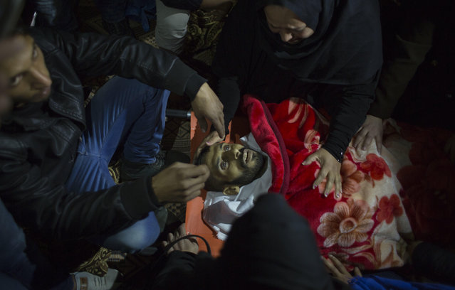 Relatives of Palestinian Muhammed al-Aqraa, who was killed in an explosion in a smuggling tunnel at the border between Gaza and Egypt, mourn over his body at his family house during his funeral, Thursday, February 9, 2017. Palestinian officials say an Israeli pre-dawn airstrike has killed several Gaza residents and wounded five others in a smuggling tunnel along the border with Egypt. The bombing appears to be the first to target smuggling tunnels since the 2014 war between Israel and Gaza's Hamas rulers. (Photo by Khalil Hamra/AP Photo)