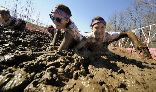 Teammates Shelbie Gilbert, of Dornsife, Pa., left, and Laura Bosack of Minersville, Pa., crawl through a mud pit obstacle on Saturday, May 2, 2015 during the Dirty Girl Mud Run at Montage Mountain in Scranton, Pa. (Photo by Butch Comegys/The Scranton Times-Tribune via AP Photo)
