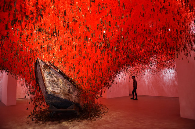 "A visitor looks at ""The Key in the Hand"" a piece of art by Japanese artist Chiharu Shiota presented at Japan's pavilion during the 56th International Art Exhibition (Biennale d'Arte) titled ""All the World's Futures"" on May 5, 2015 in Venice. (Photo by Gabriel Bouys/AFP Photo)"