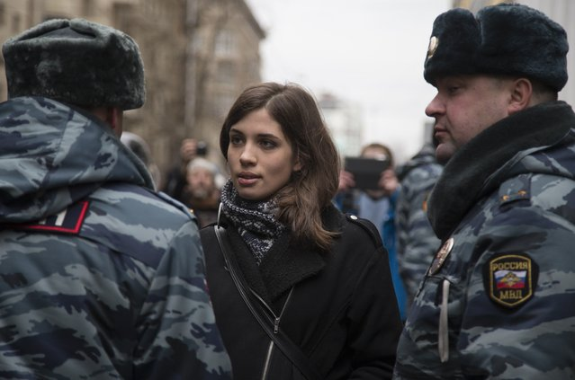 Member of the p*ssy Riot punk group, Nadezhda Tolokonnikova, center, speaks to a police officer outside Zamoskvoretsky District Court in Moscow, Russia, Monday, February 24, 2014, where hearings started against opposition activists detained on May 6, 2012 during the rally at Bolotnaya Square. A Moscow judge on Friday, February 21, 2014, convicted eight anti-government protesters of rioting during a 2012 protest against Vladimir Putin, following a trial seen as part of the Kremlin's efforts to stifle dissent. (Photo by Alexander Zemlianichenko/AP Photo)