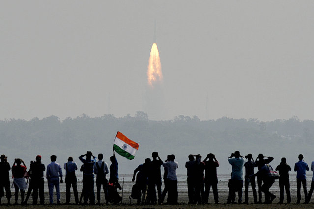 Indian onlookers watch the launch of the Indian Space Research Organisation (ISRO) Polar Satellite Launch Vehicle (PSLV-C37) at Sriharikota on Febuary 15, 2017. India successfully put a record 104 satellites from a single rocket into orbit on February 15 in the latest triumph for its famously frugal space agency. Scientists who were at the launch in the southern spaceport of Sriharikota burst into applause as the head of India's Space Research Organisation (ISRO) announced all the satellites had been ejected. (Photo by Arun Sankar/AFP Photo)