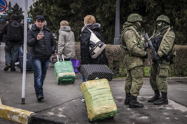 Armed men patrol the street outside Simferopol's airport in the Crimea region of Ukraine, on February 28, 2014. As the possibility of a showdown between Ukraine's fledgling government and the Kremlin appeared to grow Friday, armed men whose uniforms bore no insignia took up positions at the Simferopol and Belbek airports as Interior Minister Arsen Avakov warned of a direct provocation, but there was no sign of any violence. (Photo by Sergey Ponomarev/The New York Times)