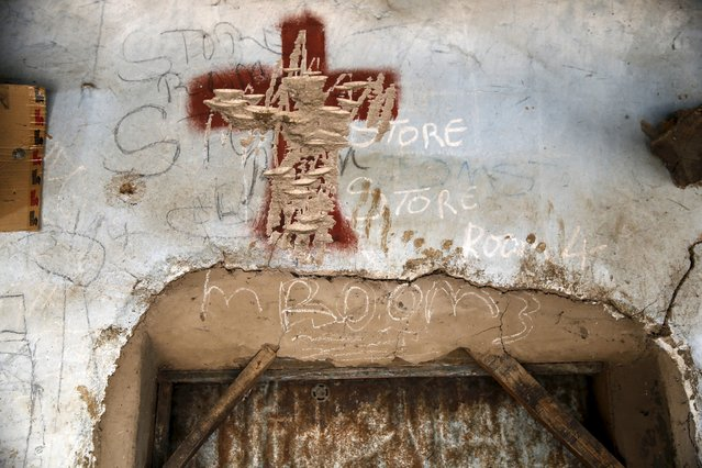 A cross sign inscribed at the entrance of a room is seen chiselled in a compound once occupied by Boko Haram in Michika town, after the Nigerian military recaptured it from Boko Haram, in Adamawa state May 10, 2015. (Photo by Akintunde Akinleye/Reuters)