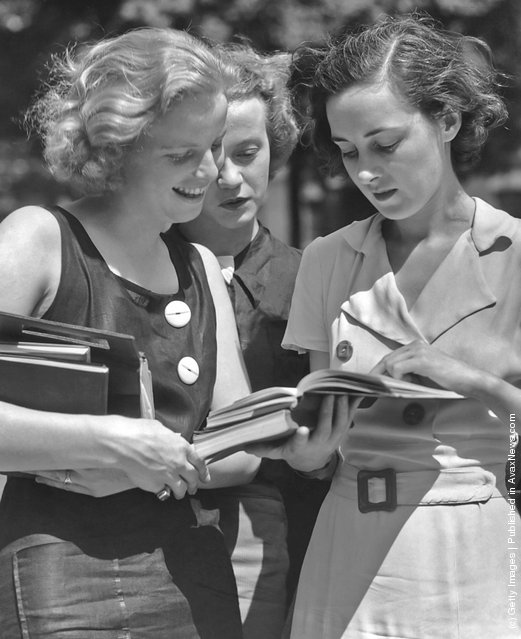 Three female students reading a book circa 1950's