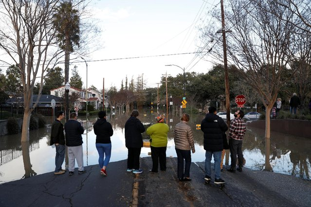 People stand by a flooded street near William Street Park after heavy rains overflowed nearby Coyote Creek in San Jose, California, U.S., February 21, 2017. (Photo by Stephen Lam/Reuters)