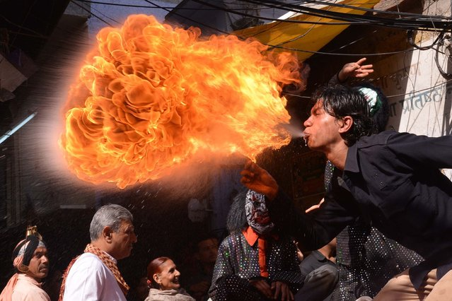 An Indian Hindu devotee performs with fire as he participates in a procession ahead of the Holi festival in Amritsar on March 12, 2014. Holi, the popular Hindu spring festival of colours is observed in India at the end of the winter season on the last full moon of the lunar month and will be celebrated on March 16 this year. (Photo by Narinder Nanu/AFP Photo)