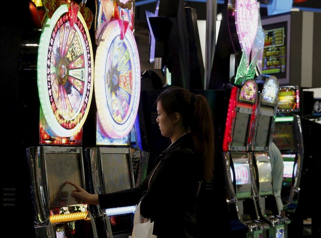 A visitor tries a slot machine at the Global Gaming Expo (G2E) Asia in Macau, China May 19, 2015. (Photo by Bobby Yip/Reuters)