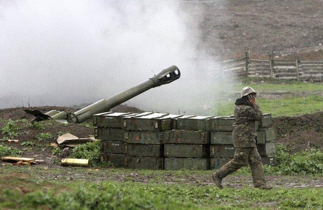 An Armenian covers his ears while a howitzer fires at an artillery position of the self-defense army of Nagorno-Karabakh near Martakert, Azerbaijan, Sunday, April 3, 2016. (Photo by Vahram Baghdasaryan/Photolure Photo via AP Photo)