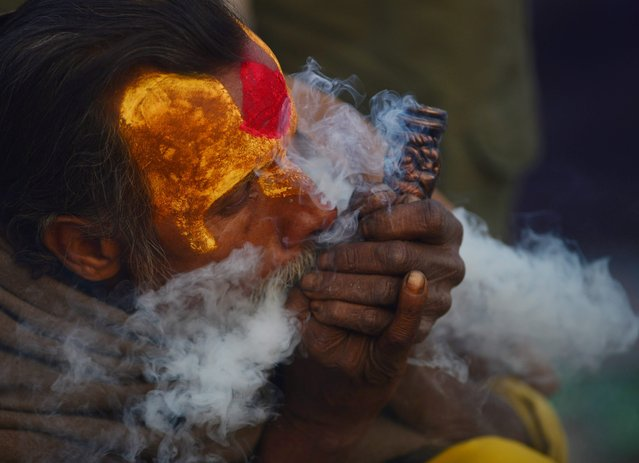 A Nepalese Sadhu (Hindu holy man) smokes a chillum, a traditional clay pipe, as a holy offering to Lord Shiva, the Hindu god of creation and destruction near the Pashupatinath Temple in Kathmandu on Febuary 23, 2017, on the eve of the Hindu festival Maha Shivaratri. (Photo by Prakash Mathema/AFP Photo)
