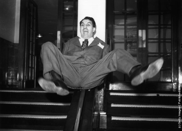1950: American comedian and actor Danny Thomas sliding down the bannisters at a reception given in his honour