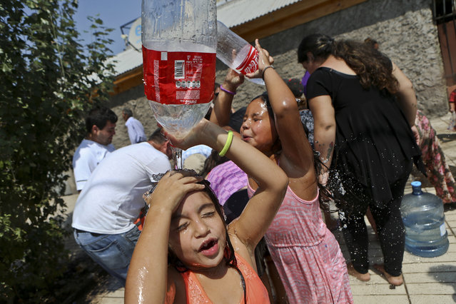 Two girls play refresh themselves while residents gather water from a fire hydrant at a neighborhood in Santiago, Chile, Monday, February 27, 2017. Millions are without potable water in Santiago's metropolitan area after floods and mudslides cut supplies. (Photo by Esteban Felix/AP Photo)