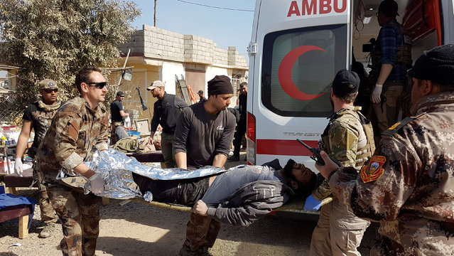 Iraqi Counter-Terrorism Service (CTS) members help a wounded civilian who fled the violence in western Mosul, Iraq February 26, 2017. (Photo by Mahdi Talaat/Reuters)