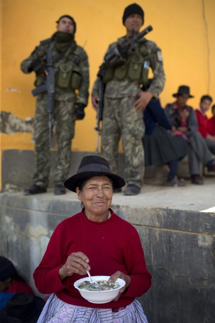 A woman eats lunch as soldiers stand guard in Surcubamba, Peru, Thursday, May 21, 2015. (Photo by Rodrigo Abd/AP Photo)