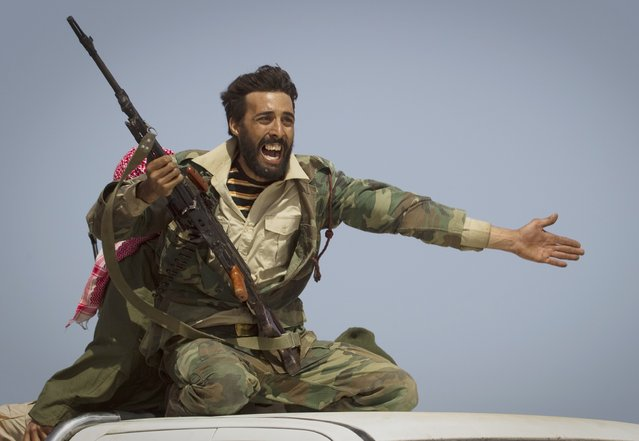 A Libyan rebel urges people to leave, as shelling from Gadhafi's forces started landing on the frontline outside of Bin Jawaad, 150 km east of Sirte, central Libya, Tuesday, March 29, 2011. (Photo by Anja Niedringhaus/AP Photo)