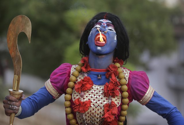 An Indian man dressed as Hindu Goddess Kali participates in a procession to celebrate the Ram Navami festival in Allahabad, India, Friday, April 15, 2016. Hindu devotees celebrate the festival of Ram Navami, the birth anniversary of Lord Rama, which also marks the end of the nine-day long fasting and Navaratri festival. (Photo by Rajesh Kumar Singh/AP Photo)