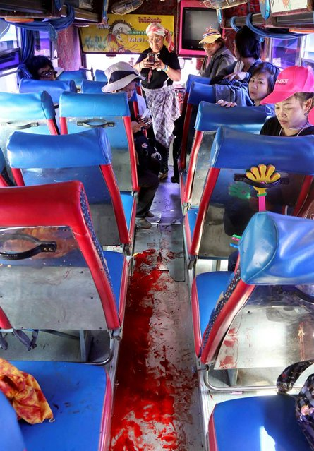 Anti-government protesters look at bloodstained floor of the bus they were traveling after an attack by suspected gunmen while on their way back from a protest in Bangkok, Thailand Tuesday, April 1, 2014. Gunmen have fired on a convoy of anti-government protesters in Thailand's capital, and four people have been wounded. (Photo by AP Photo)