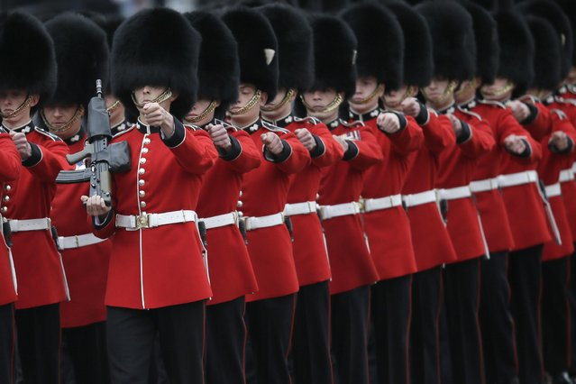 """Soldiers march outside Buckingham Palace during the Trooping The Colour parade at Buckingham Palace, in London, Saturday, June 13, 2015. Hundreds of soldiers in ceremonial dress have marched in London in the annual Trooping the Color parade to mark the official birthday of Queen Elizabeth II. The Trooping the Color tradition originates from preparations for battle, when flags were carried or """"trooped"""" down the rank for soldiers to see. (AP Photo/Tim Ireland)"""