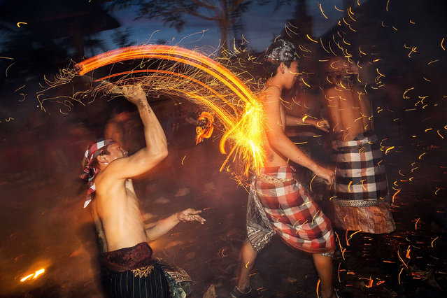 """A Balinese man hits another with a burned coconut husk during the """"Mesabatan Api"""" ritual a head of Nyepi Day on March 30, 2014 in Gianyar, Bali, Indonesia. Mesabatan Api is held annually a day before the Nyepi Day of Silence, as symbolizes the purification of universe and human body trough fire. Nyepi is a Hindu celebration observed every new year according to the Balinese calendar. (Photo by Agung Parameswara/Getty Images)"""